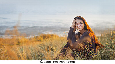 Portrait of the beautiful brunette woman at the windy autumn...