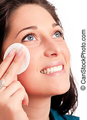 Young woman removing makeup with cleansing pad isolated on...