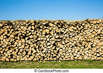 firewood - Pile of chopped firewood with green grass and...