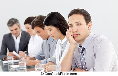Attractive businessman bored at a presentation with his team