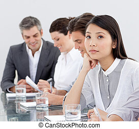 Upset asian businesswoman bored at a presentation with her...