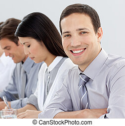 Attractive businessman at a conference with his team in the...