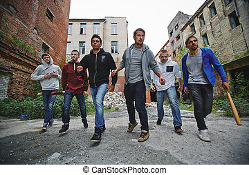 Malicious guys - Group of spiteful hooligans walking along...