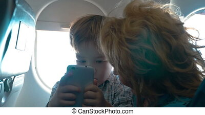 Grandmother and grandson with cell in the plane