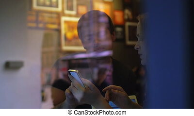 Woman and man talk in the restaurant using smartphone - Slow...