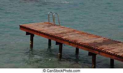 Sea ramp above the water with pool ladder for swimmers and...