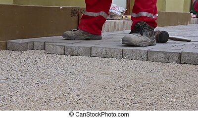 Masons hands are fitting flagstone. - Close up view of...