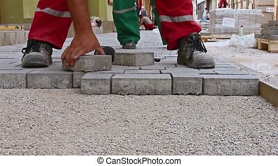 Masons hands are fitting flagstone - Close up view of...