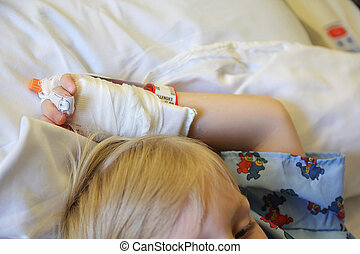 Childs Hand With IV in it at Hospital - A child is laying on...
