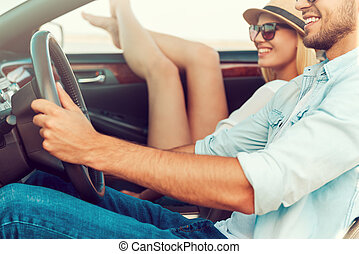 It is so good to get away out of the city. Happy young woman relaxing on the front seat while her boyfriend sitting near and driving convertible