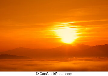 sun at sunset with low fog - orange sunset with sun at...
