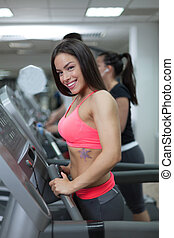 People at the gym exercising on cross trainers