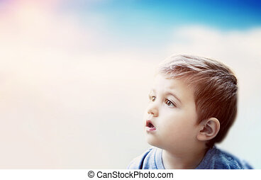 Boy looking at the sky with surprised expression Child...
