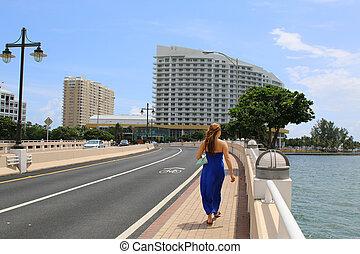 Beautiful casual woman walking in downtown Miami Financial...