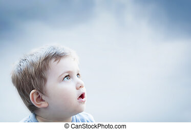 Boy looking at the sky with surprised expression. Child...