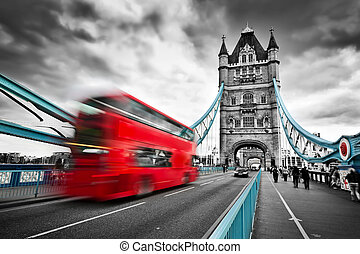 Red bus in motion on Tower Bridge in London, the UK....