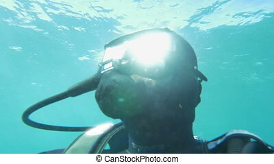 Scuba diver in blue water on sunny day