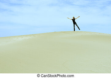 girl standing on top of a dune