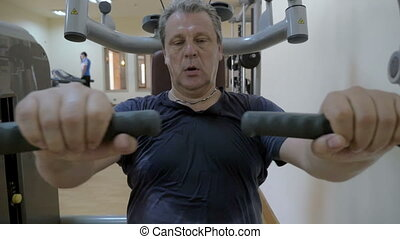 Sweaty man working out on exercise machine - Slow motion of...