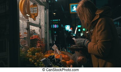 Young woman buys products in the stall outside