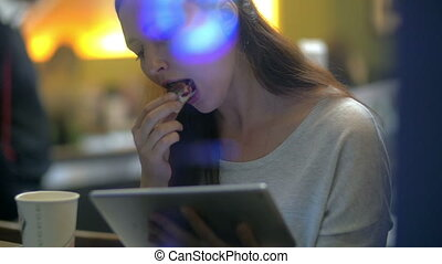 Brunette woman eats cake while reading on electronic tablet...