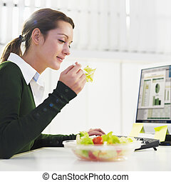 woman eating salad in office. Copy space
