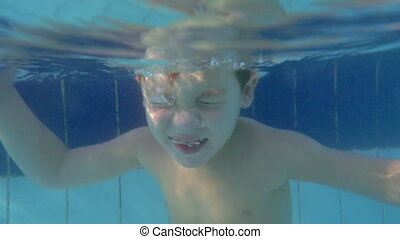 Fun in the pool on resort - Slow motion of a child diving...