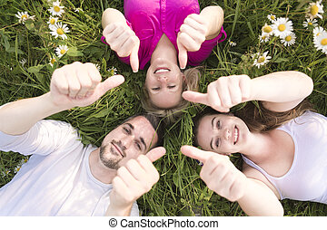 happy friends spending free time together in a field - Three...
