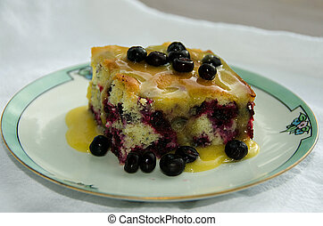 Huckleberry cake with a vanilla butter sauce poured over the...