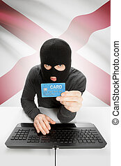 Hacker holding credit card with US state flag on background - Alabama