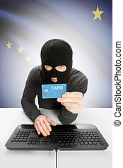 Hacker holding credit card with US state flag on background - Alaska