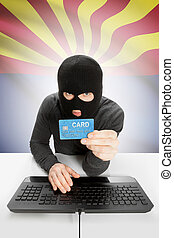 Hacker holding credit card with US state flag on background...