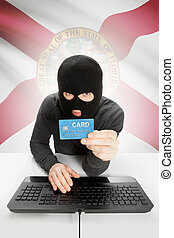 Hacker holding credit card with US state flag on background - Florida