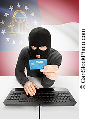 Hacker holding credit card with US state flag on background - Georgia