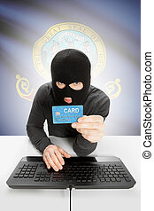 Hacker holding credit card with US state flag on background - Idaho