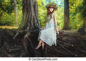 Girl sits on a tree in the fairy forest On her head a wreath...