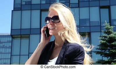 Business woman talking on cellular phone on the background...