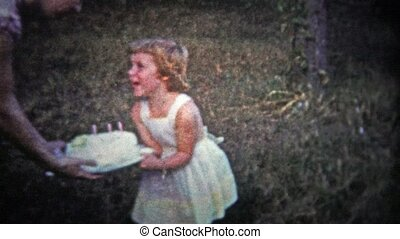 TENNESSEE, USA - 1954: Woman presents birthday cake - Unique...