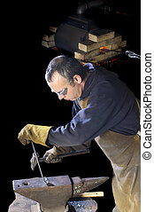 Blacksmith working on decorative handrail bending the heated...
