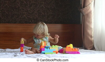 little blonde girl plays with toy constructor on sofa