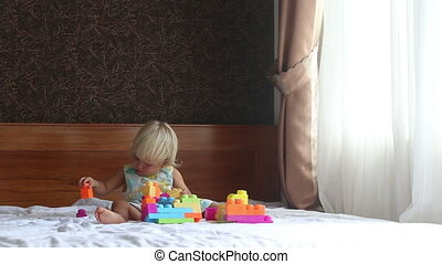 little blonde girl plays with toy constructor on sofa at...