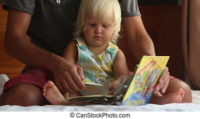 little girl turns over pages of book on father's knees on sofa