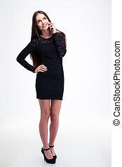 Happy woman in black dress talking on smartphone - Full...