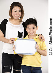 Asian mother and son with blank white board and looking...