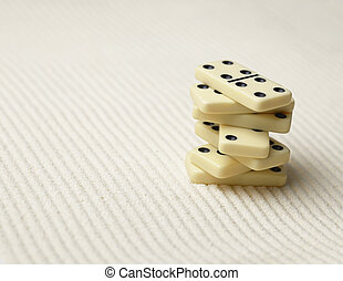 Dominoes pile on surface of sand - an abstract composition -...