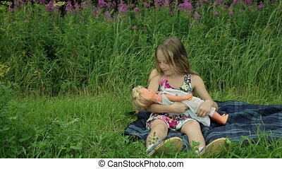 young girl playing with doll on outside grass
