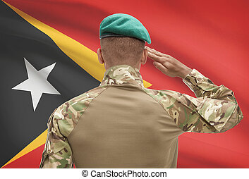 Dark-skinned soldier with flag on background - East Timor -...