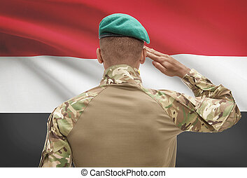 Dark-skinned soldier with flag on background - Egypt -...
