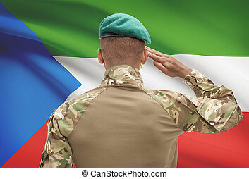 Dark-skinned soldier with flag on background - Equatorial...