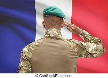 Dark-skinned soldier with flag on background - France -...